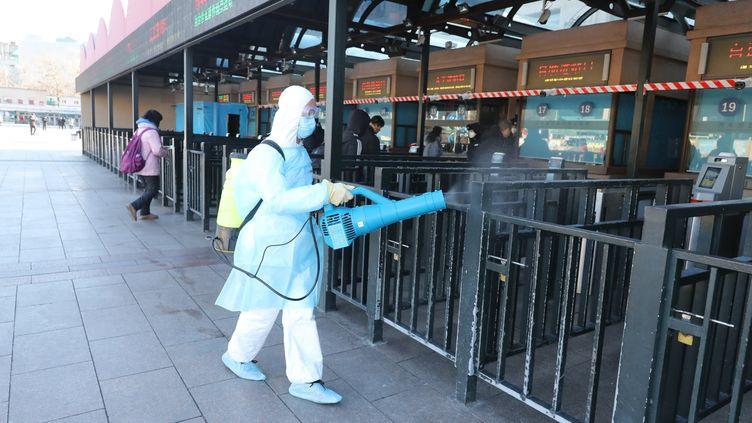 Un agent de santé désinfecte les salles de départ et d'attente de la gare de Pékin, le 4 février 2020. (KOKI KATAOKA / YOMIURI)