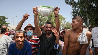 Des partisans du président tunisienKaïs Saïdexhibent une couche de bébé le 26 juillet 2021, alors qu'ils sont rassemblés devant le bâtiment du Parlement tunisien au Bardo, dans la capitale Tunis, pour soutenir lechef de l'Etataprès sa décision, entres autres, de geler les travaux de l'Assemblée. (CHEDLY BEN IBRAHIM / HANS LUCAS)