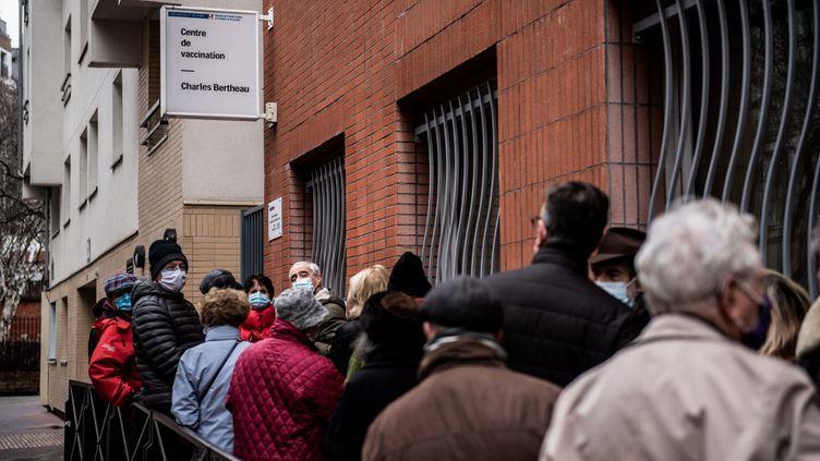 Des personnes patientent devant un centre de vaccination contre le Covid-19, le 15 janvier 2021 à Paris. (MARTIN BUREAU / AFP)