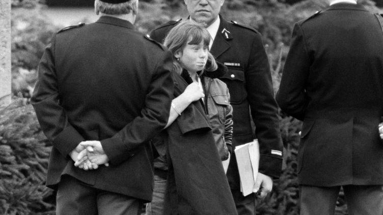 Murielle Bolle, alors âgée de 15 ans, entourée de policiers à Epinal (Vosges), le 5 novembre 1984. (JEAN-CLAUDE DELMAS / AFP)