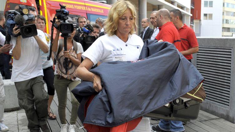 Une infirmière ramène dans un couffin le nourisson enlevé dans la nuit de lundi à mardi 28 août 2012 à l'hôpital Saint-Joseph de Marseille. (FRANCK PENNANT / AFP)