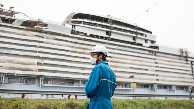 """Un travailleur des Chantiers de l'Atlantique devant le """"Wonders of the sea"""", le 8 octobre 2020 à Saint-Nazaire (Loire-Atlantique). (JEREMIE LUSSEAU / HANS LUCAS / AFP)"""