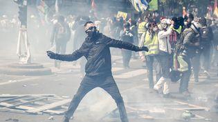 Un manifestant lance un projectile sur les forces de l'ordre avant le départ du cortège syndical à Paris, le 1er mai 2019. (ZAKARIA ABDELKAFI / AFP)