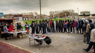 Des bénévoles distribuent des repas à des migrants le 22 mars 2017 à Calais (Pas-de-Calais). (PHILIPPE HUGUEN / AFP)