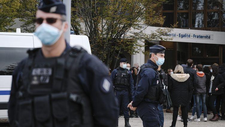 Des policiers en faction devant le collège du Bois d'Aulne à Conflans-Sainte-Honorine où enseignait Samuel Paty. (ARNAUD DUMONTIER / MAXPPP)