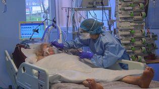 Une infirmière s'occupe d'une malade atteinte de Covid-19, le 13 mars 2020 à l'hôpital Bichat à Paris. (ANNE CHAON / AFP)