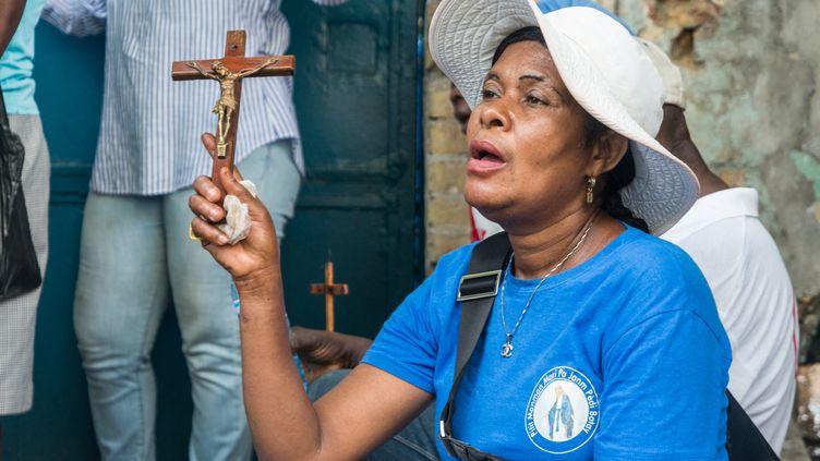 Une femme prinant pour la libération des religieux, le2avril 2021 à Port-au-Prince (Haïti). (REGINALD LOUISSAINT JR / AFP)