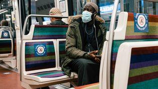 Un homme muni d'un masque dans le métro parisien, dont certains sièges sont condamnés par des stickers en raison de l'épidémie de coronavirus, le 9 mai 2020. (KARINE PIERRE / HANS LUCAS / AFP)