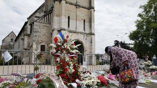 Une femme musulmane dépose des fleurs devant l'église Saint-Etienne de Saint-Etienne-du-Rouvray (Seine-Maritime), en hommage au prètre tué à l'arme blanche par des terroristes, vendredi 29 juillet. (CHARLY TRIBALLEAU / AFP)