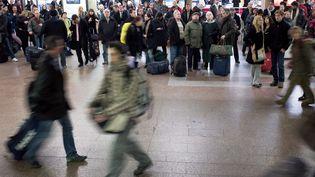Des voyageurs observent les panneaux d'affichage des trains dans la gare de Lyon Part-Dieu, le 4 mars 2009. (JEAN-PHILIPPE KSIAZEK / AFP)