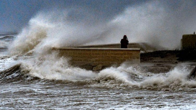 Une personne prend des photos alors que les vagues frappent la plage d'El Saler en Espagne en pleine tempête Gloria, le 20 janvier 2020 (JOSE JORDAN / AFP)