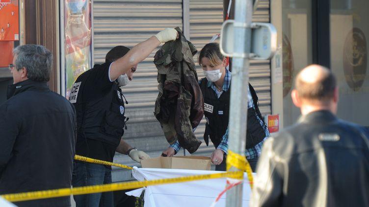 Des policiers prélèvent un uniforme militaire couvert de sang, à Montauban(Tarn-et-Garonne), après le meurtre de deux soldats, le 15 mars 2012. (ERIC CABANIS / AFP)