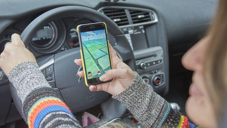 """Une utilisatrice de """"Pokémon Go"""" joue au volant de sa voiture dans les rues de Nancy, le 3 juillet 2016. (MAXPPP)"""