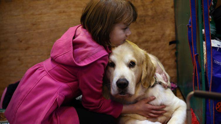 Une fillette fait un câlin à son chienà Birmingham (Royaume-Unis), le 5 mars 2015. (CARL COURT / GETTY IMAGES EUROPE)