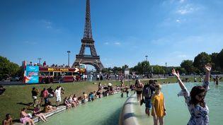 Des touristes profitent du soleil au pied de la tour Eiffel, à Paris, le 2 août 2018. (GERARD JULIEN / AFP)