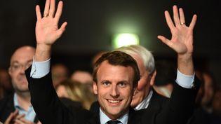 """Emmanuel Macron lève les mains à un meeting de son mouvement """"En marche"""" au Mans, le 11 octobre 2016. (JEAN-FRANCOIS MONIER / AFP)"""