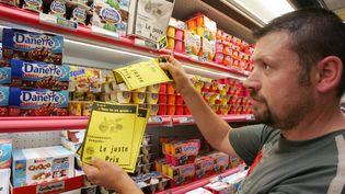 Un éleveur place un tract dans le rayon frais d'un hypermarché pour alerter les consommateurs sur l'augmentation de ses coûts de production et dénoncer les marges de la grande distribution. (ANDRE DURAND / AFP)