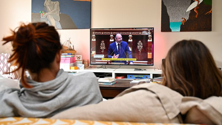 Des Français regardent une interventiondu Premier ministre à la télévision, le 28 avril 2020, à Hede-Bazouges (Ille-et-Vilaine). (DAMIEN MEYER / AFP)