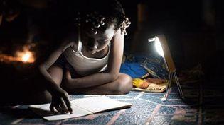 Une écolière apprend ses leçons, éclairée par une lampe solaire fabriquée au Burkina Faso par l'entreprise Lagazel en 2020 (Entreprise Lagazel)