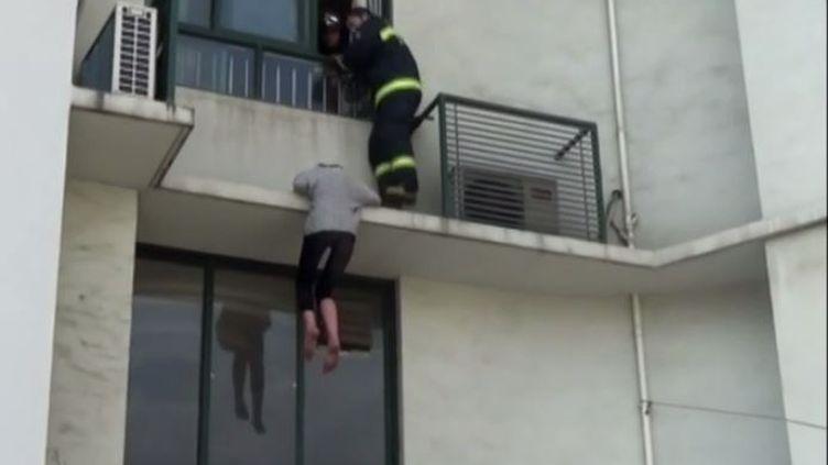 Unejeune Chinoise de 20 ans suicidaire sauvée par des pompiers, à Shanghai (Chine), le 2 avril 2015. (CCTV+ / YOUTUBE)