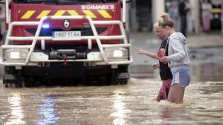 Deux femmes traversent une rue inondée deSalies-de-Béarn (Pyrénées-Atlantiques), le 13 juin 2018. (IROZ GAIZKA / AFP)