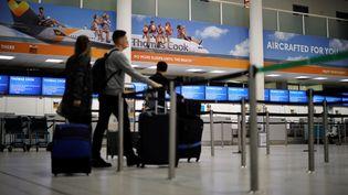 Des passagers passent devant un comptoir fermé du voyagiste Thomas Cook, à l'aéroport de Gatwick à Londres, le 23 septembre 2019. (TOLGA AKMEN / AFP)