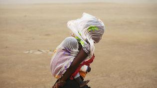 Une femme et son bébé affrontent une tempête de sable à Tombouctou (Mali), le 29 juillet 2013. (JOE PENNEY / REUTERS)