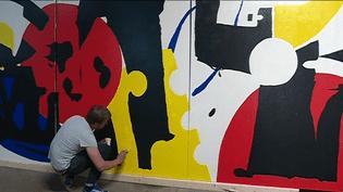 Hugues Chevallier, l'un des street artistes, est en train de réaliser sa fresque  (France 3/ Culturebox)