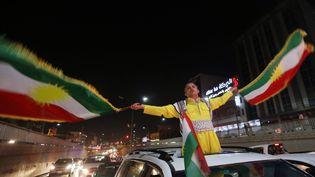 Un homme parade avec des drapeaux kurdes, le 27 septembre 2017, après l'annonce des résultats du référendum, à Erbil (Irak). (SAFIN HAMED / AFP)