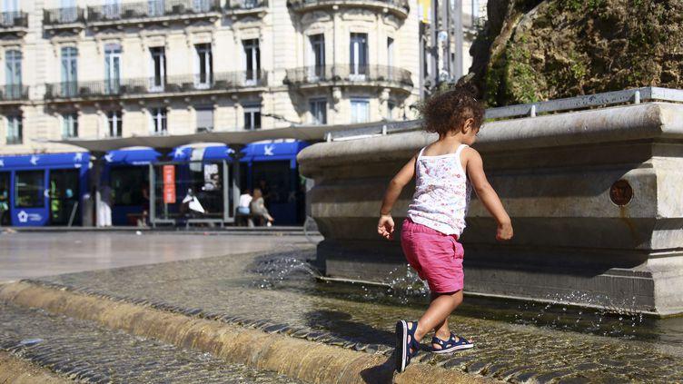 Une enfant se rafraîchit dans une fontaine, place de la Comédie à Montpellier (Hérault), le 17 juin 2018. (LODI FRANCK/SIPA)