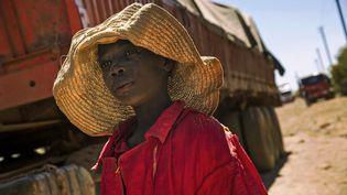 Un enfant congolais devant un camion transportant des roches extraites d'une mine de cobalt à Lubumbashi, au sud de la RDC, en mai 2016. (JUNIOR KANNAH / AFP)