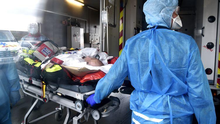 Des soignants prennent en charge un homme atteint par le Covid-19 après son transfert par hélicoptère depuis Lyon (Rhône), le 12 novembre 2020 à Strasbourg (Bas-Rhin). (FREDERICK FLORIN / AFP)