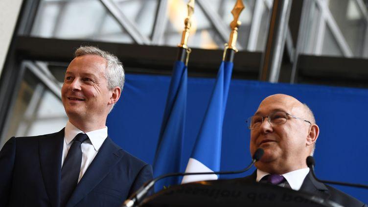 Le ministre de l'Economie, Bruno Le Maire, et son prédécesseur, Michel Sapin, le 17 mai 2017 à Bercy (Paris). (CHRISTOPHE ARCHAMBAULT / AFP)