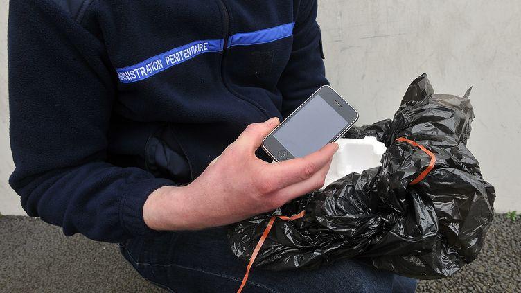 Un surveillant montre un téléphone portable jeté par-dessus les murs de la prison de Sequedin (Nord), le 16 avril 2013. (  MAXPPP)