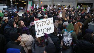 Descentaines de personnes manifestent, samedi 28 janvier 2017, devant l'aéroport JFK à New York contre le décret anti-immigration de Donald Trump. (MOHAMMED ELSHAMY / ANADOLU AGENCY / AFP)