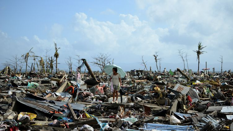 Une femme au milieu des décombres, après le passage du typhon Haiyan, à Tacloban (Philippines), le 11 novembre 2013. (NOEL CELIS / AFP)