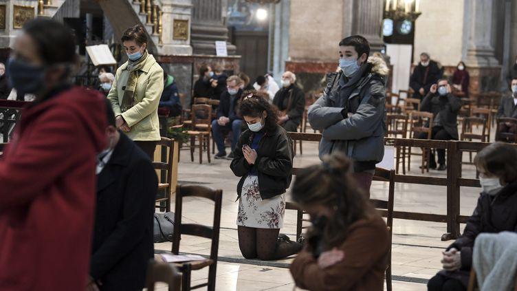 Des personnes prient dans l'église Saint-Sulpice à Paris, le 29novembre 2020. (ALAIN JOCARD / AFP)