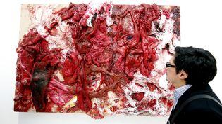 Un spectateur observe une œuvre sanguinolente de l'artiste indo-britannique Anish Kapoor exposée à la Fiac, à Paris, le 21 octobre 2015. (FRANCOIS GUILLOT / AFP)
