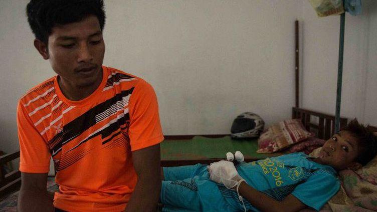 Ce garçon de 13 ans a perdu plusieurs de ses doigts alors qu'il travaillait au champ avec sa famille. Sa pelle a heurté une bombe non explosée datant de la guerre du Vietnam. Ici, avec son frère aîné (à gauche) à l'hôpital de Xieng Khouang, dans le nord du Laos. (ALISON MCCAULEY / AFP)