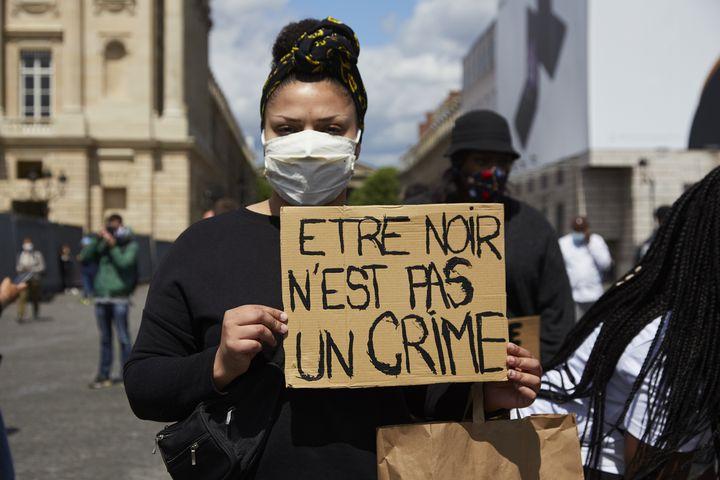 """Une manifestante présente une pancarte sur laquelle est écrit """"être noir n'est pas un crime"""", à Paris, le 6 juin 2020. (ADNAN FARZAT / NURPHOTO)"""