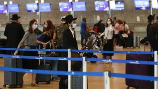 Des passagers portant des masques à l'aéroport Ben Gourion de Tel Aviv le 24 septembre 2020 (AHMAD GHARABLI / AFP)