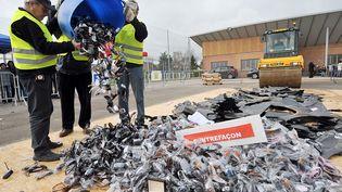 Douaniers déversant des contrefaçons avant leur destruction en décembre 2009. (PHILIPPE HUGUEN / ARCHIVES)