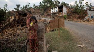 Des enfants errent dans un village détruit du Népal, le 2 mai 2015, une semaine après le séisme qui a ravagé le pays. (DANISH SIDDIQUI / REUTERS)