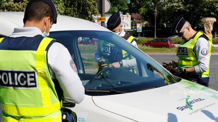 Des policiers contrôlent un véhicule à la sortie de Paris, le 20 avril 2020. (FRANCOIS GUILLOT / AFP)