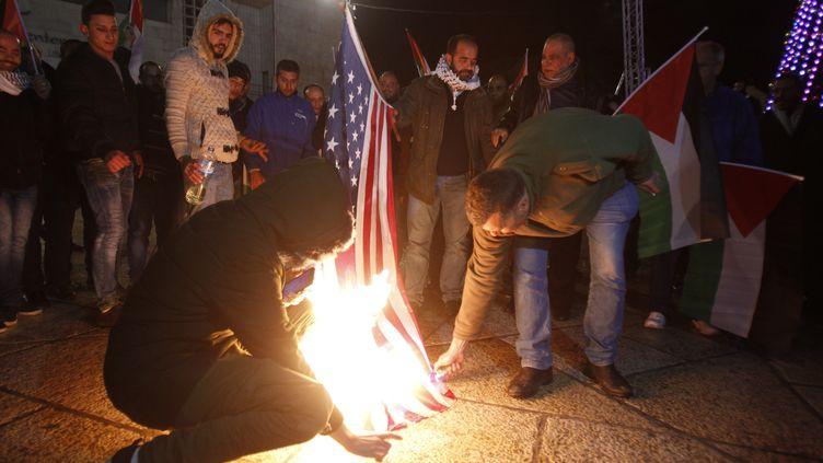 Des manifestants palestiniens brûlent un drapeau américain à Bethléem, en Cisjordanie (territoires palestiniens), le 6 décembre 2017. (MUSA AL SHAER / AFP)