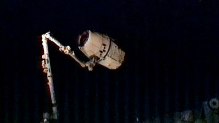 Le bras robotique, piloté par deux astronautes de l'ISS, attrape la capsule Dragon, le 25 mai 2012. (AFP PHOTO / NASA)