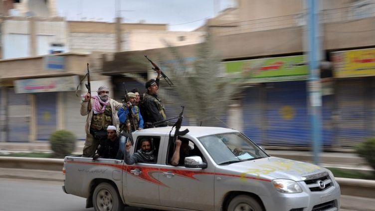 Des rebelles syriens célèbrent la prise de Raqa, dans le nord du pays, le 4 mars 2013. ( AFP )