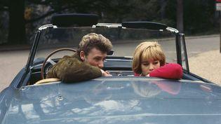 1963 : le couple vedette Johnny Halliday et Sylvie Vartan posent dans la nouvelle Ferrari qu'ils viennent d'acheter. (MICHAEL HOLTZ / AFP)