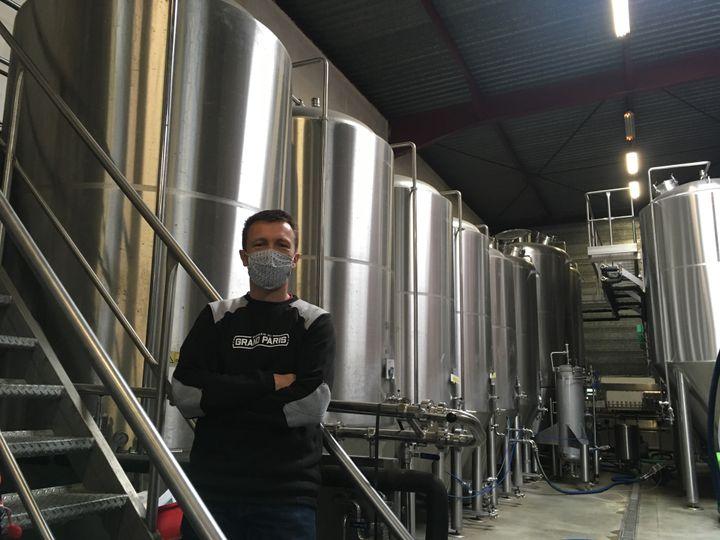 Frabrice Le Goff, cogérant de la brasserie du Grand Paris, devant les fûts de brassage de la bière, remis en activité ces derniers jours, le 5 mai 2021. (GRÉGOIRE LECALOT / RADIO FRANCE)