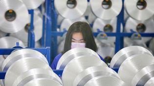 Une employée d'une entreprise de textile, à Nantong, dans la province du Jiangsu(Chine). (STR / AFP)